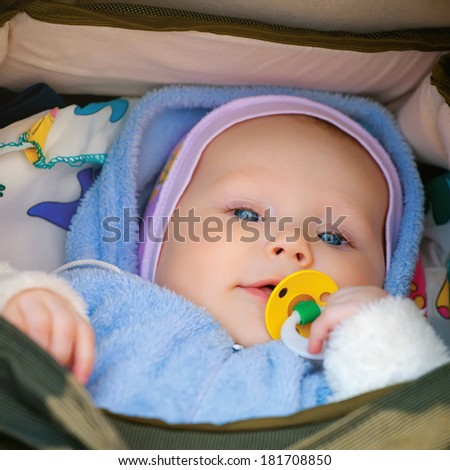 Smiling little girl with a pacifier in his mouth in his wheelchair - stock photo