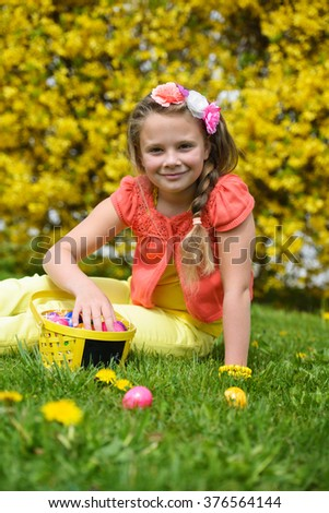Smiling  little girl with basket full of colorful easter eggs outdoors - stock photo