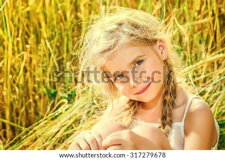 Smiling little girl with beautiful blonde hair sitting in the wheat field on a bright sunny day. Summer holidays.  - stock photo