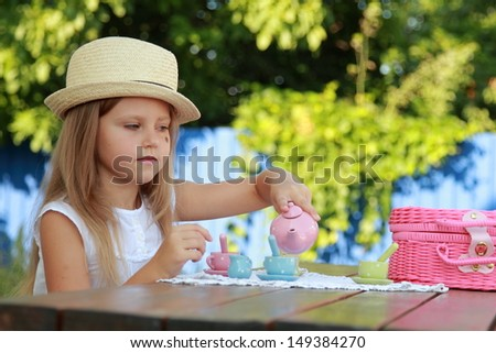 Smiling little girl with beautiful long blond hair wearing a straw hat playing with toy dishes for tea outdoors