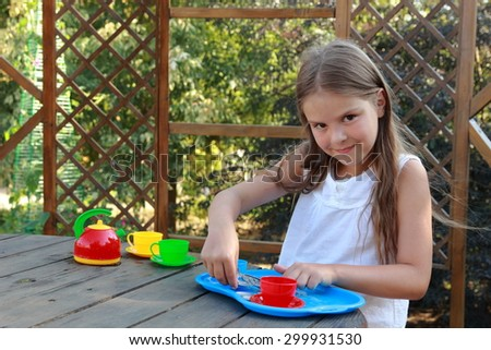 Smiling little girl with beautiful long hair wearing a bandana playing with toy dishes for tea outdoor - stock photo