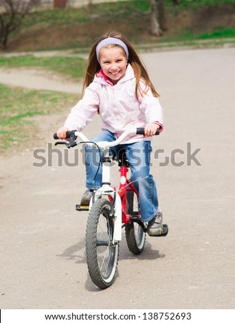 Smiling little girl with bicycle on road