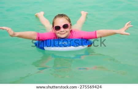 Smiling little girl with blue life ring has fun in the water - stock photo