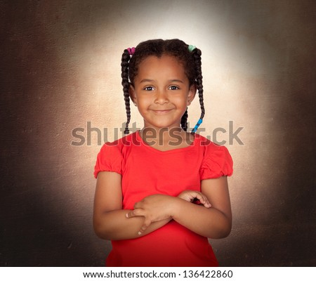 Smiling little girl with her crossed arms on a over brown background - stock photo