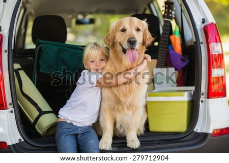 Smiling little girl with her dog in car trunk on a sunny day - stock photo