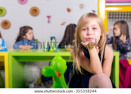 Smiling little girl with her friends at birthday party