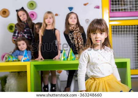 Smiling little girl with her friends at birthday party - stock photo