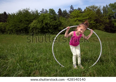 Smiling Little Girl With Hula Hoop Enjoying Beautiful Spring Day In The Park - stock photo