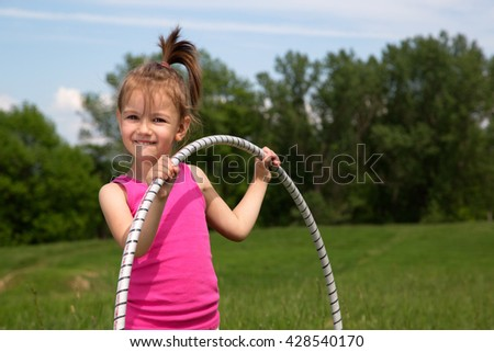 Smiling Little Girl With Hula Hoop Enjoying Beautiful Spring Day In The Park