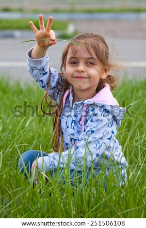 Smiling little girl with pile in hand, outdoors - stock photo