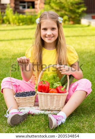 Smiling little girl with vegetables and berry