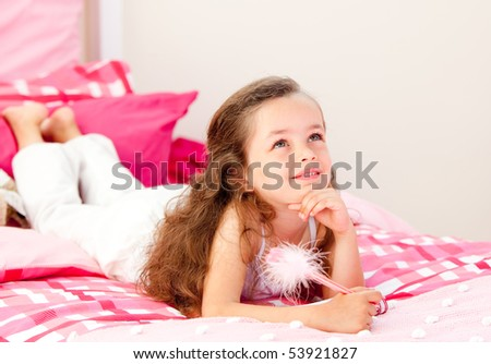 Smiling little girl writing on a notebook lying on her bed at home