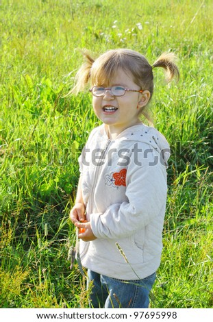 Smiling little girl 2 years old in glasses on the meadow - stock photo