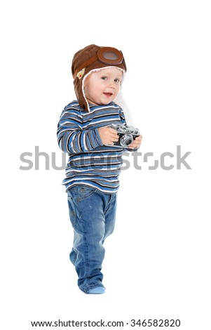 Smiling little Kid boy dressed in jeans, t-shirt and  aviator helmet with photo camera in hands. Isolated on white background