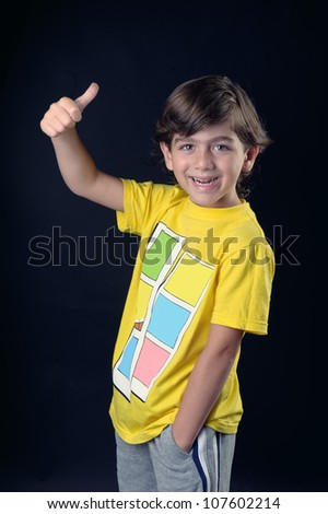 Smiling little kid with thumbs up sign, - stock photo