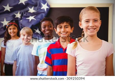 Smiling little school kids in school corridor against american flag on chalkboard - stock photo