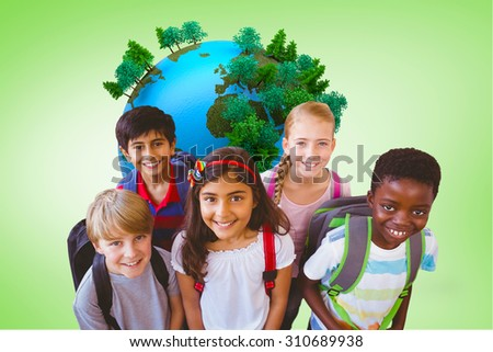 Smiling little school kids in school corridor against green vignette - stock photo