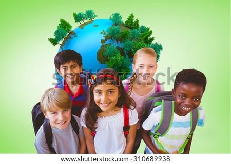 Smiling little school kids in school corridor against green vignette - stock photo