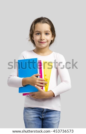 Smiling little student girl holding notebooks