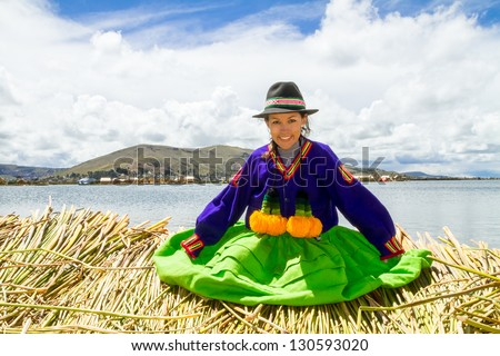 Smiling local girl Sitting on a floating Uros island on the shore of lake Titicaca - stock photo