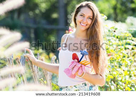 Smiling long-haired girl florist working in roses plants at summer garden