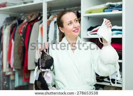 Smiling long-haired woman choosing bra at bedroom - stock photo