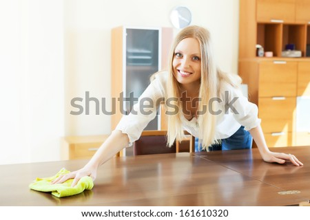 Smiling long-haired woman cleaning table at home - stock photo