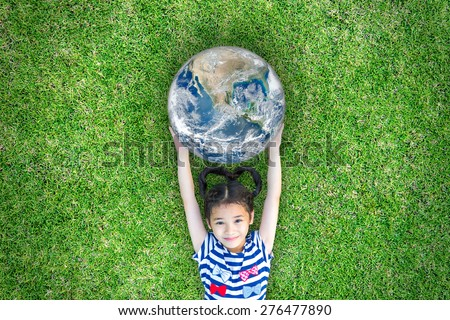 Smiling lovely happy kid holding a globe lying on grass floor: Healthy cute little child love the planet: Children saving eco green environment CSR concept: Element of this image furnished by NASA   - stock photo
