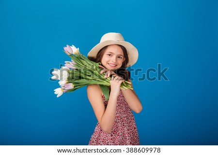 Smiling lovely little girl in hat holding bouquet of flowers on her shoulder over blue background - stock photo