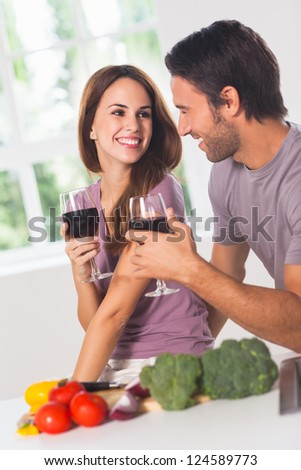 Smiling lovers with wine and vegetables in kitchen