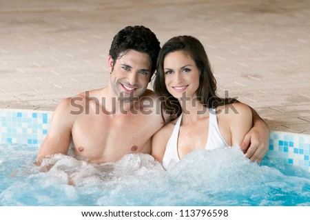 Smiling loving couple relaxing together on a jacuzzi pool at spa