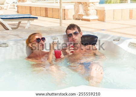Smiling loving couple relaxing together on a jacuzzi pool at tourist resort - stock photo