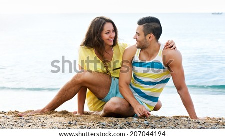 Smiling loving couple spending free time at seaside in summer day - stock photo