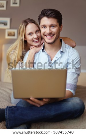 Smiling loving young couple relaxing with a laptop computer as they sit together on a bed at home or in a hotel during a vacation