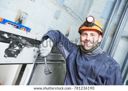 smiling machinist with spanner adjusting lift in elevator shaft