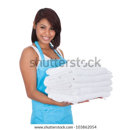 Smiling maid woman with towels. Isolated on white