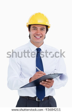 Smiling male architect with clipboard and pen against a white background - stock photo