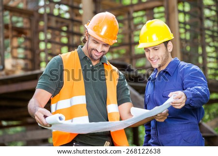 Smiling male architects analyzing blueprint outside at construction site - stock photo