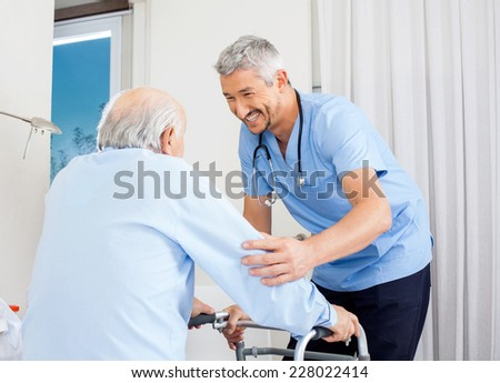 Smiling male caretaker helping senior man to use walking frame in bedroom at nursing home - stock photo