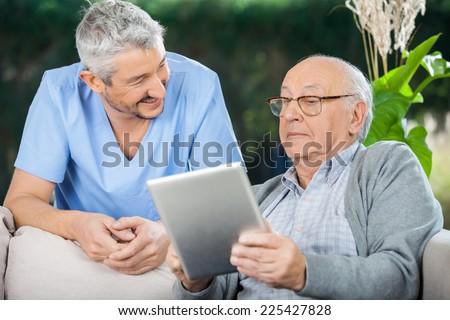 Smiling male caretaker looking at senior man using tablet computer at nursing home porch - stock photo