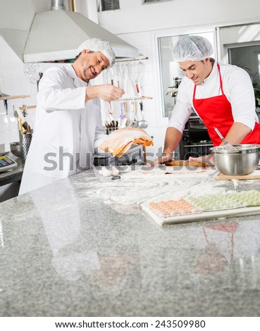 Smiling male chefs cooking ravioli pasta together at counter in commercial kitchen - stock photo