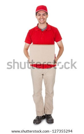 Smiling male courier in a red shirt and cap delivering a parcel in a brown cardboard box