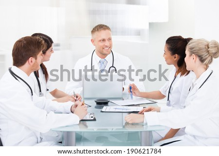 Smiling male doctor discussing with colleagues at desk in clinic