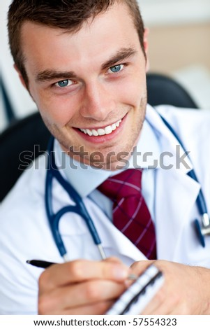 Smiling male doctor writing a prescription in his office