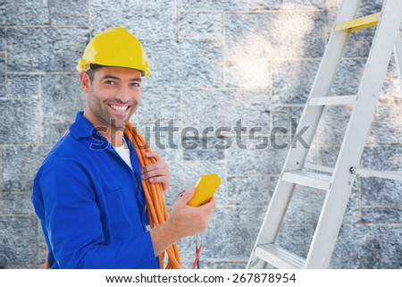 Smiling male electrician holding multimeter in office against grey - stock photo