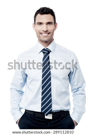 Smiling male executive posing with hands in pockets
