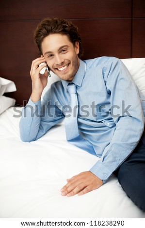 Smiling male executive relaxing in hotel room and talking to his girlfriend - stock photo