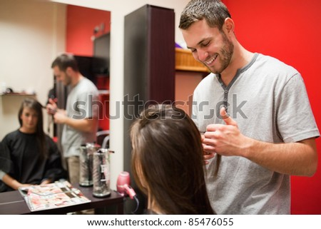 Smiling male hairdresser cutting hair with scissors - stock photo