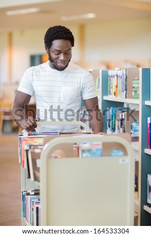 Smiling male librarian with trolley of books standing by shelves in library - stock photo