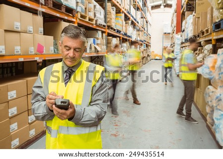 Smiling male manager using handheld in a large warehouse - stock photo